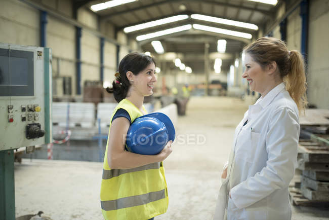 Chatting female colleagues in concrete factory — Stock Photo
