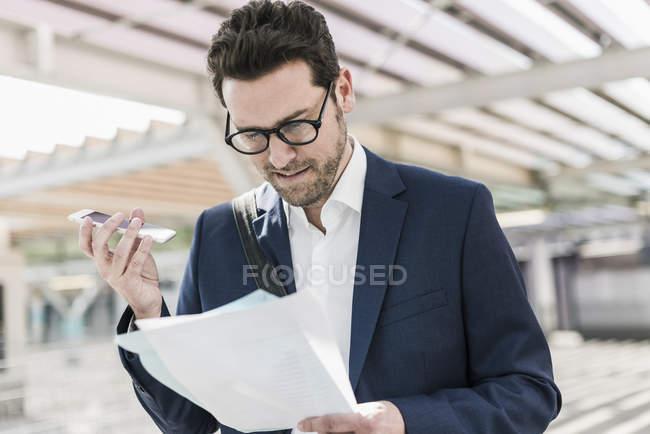 Empresario hablando notas en smartphone - foto de stock
