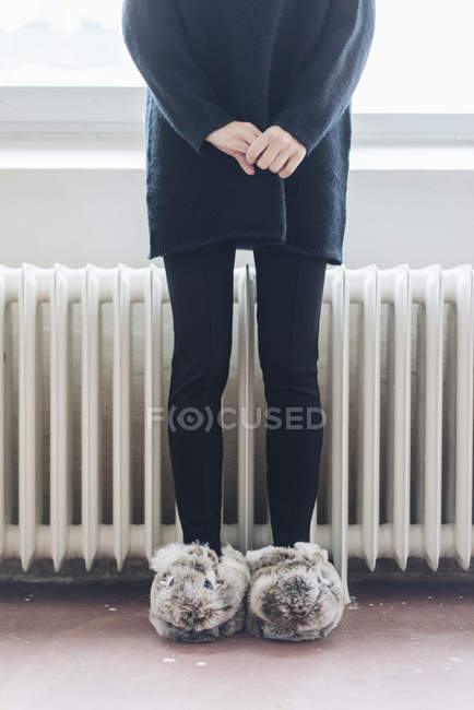 Female legs wearing fluffy slippers — Stock Photo