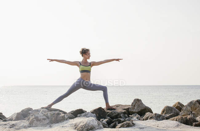 Femme pratiquant le Yoga sur la plage — Photo de stock