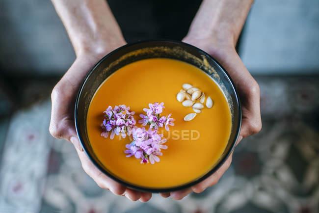 Macho mãos segurando a sopa creme de abóbora — Fotografia de Stock
