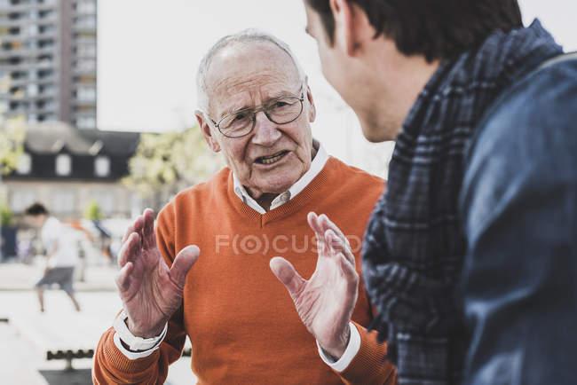 Senior man talking to adult grandson — Stock Photo