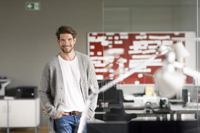Dynamic businessman standing in office, smiling — Stock Photo