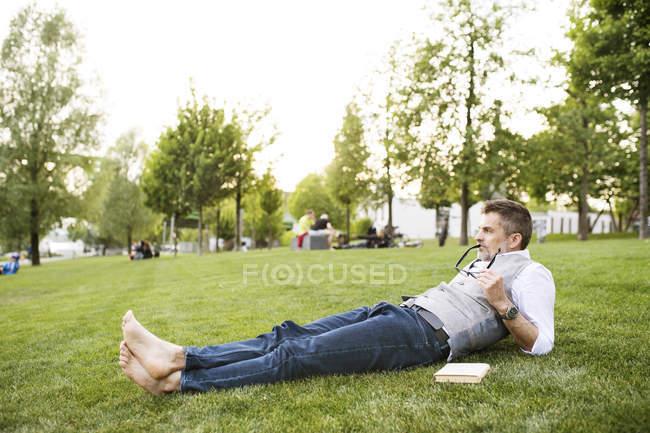 Businessman lying on grass — Stock Photo