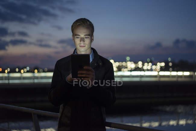 Homem usando tablet ao ar livre no crepúsculo — Fotografia de Stock