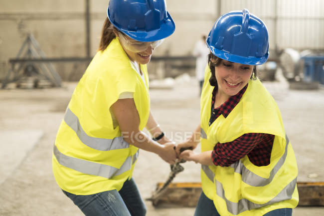 Female workers pulling machine part — Stock Photo