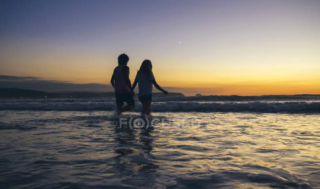 Young couple walking in sea at dusk — Stock Photo