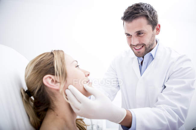 Doctor examining woman at surgery — Stock Photo