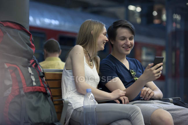 Young couple with backpacks sitting at rail station using smartphone — Stock Photo