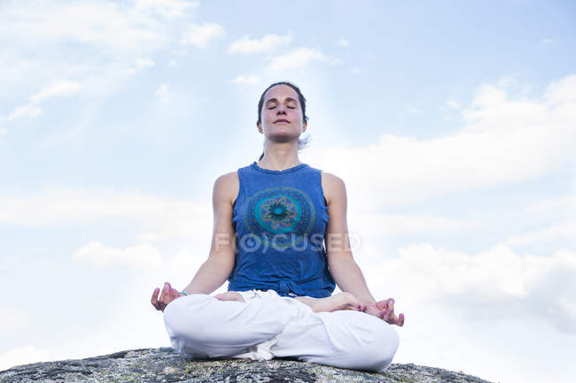 Woman in lotus pose on rock — Stock Photo