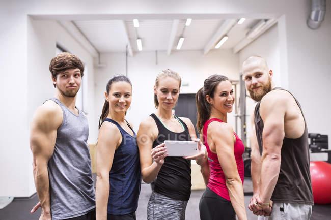 Jeunes athlètes prenant selfies dans la salle de gym — Photo de stock