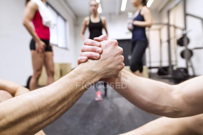 Athletes shaking hands in gym — Stock Photo