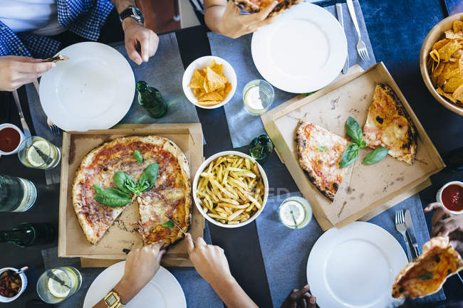 Hand cuttng pizza in box — Stock Photo