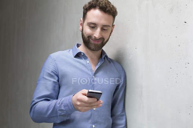 Чоловік дивиться на мобільний телефон — стокове фото