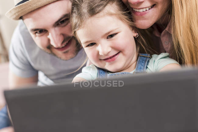 Retrato recortado de pais sorridentes e filha usando tablet — Fotografia de Stock