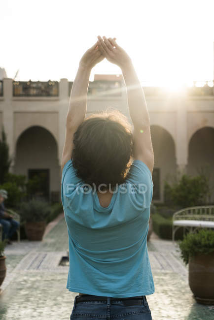 Male tourist stretching in courtyard — Stock Photo