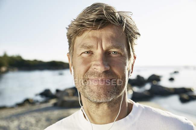 Hombre maduro con auriculares en la playa - foto de stock