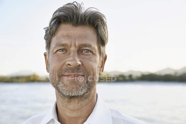 Uomo con stoppie di fronte al mare — Foto stock