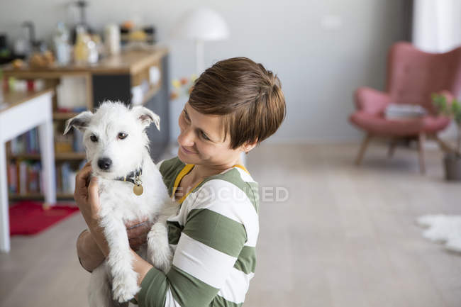 Woman holding dog on arms — Stock Photo