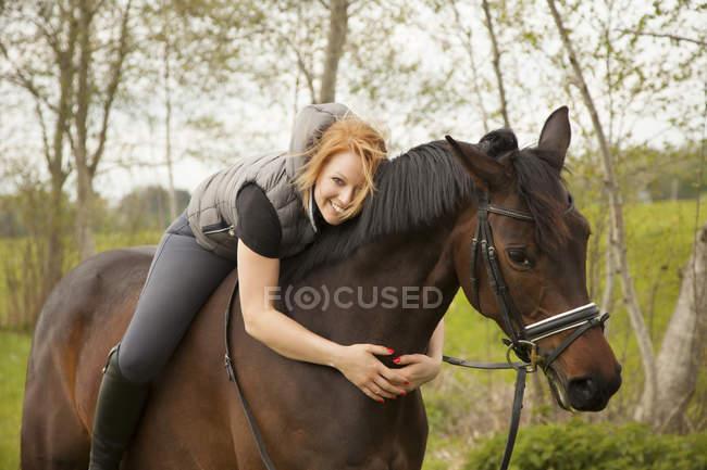 Улыбающаяся молодая женщина на лошади — стоковое фото