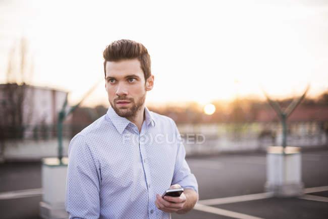 Человек с сотовый телефон стоял на открытом воздухе — стоковое фото
