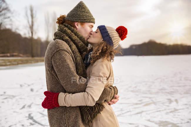 Couple kissing on frozen lake — Stock Photo