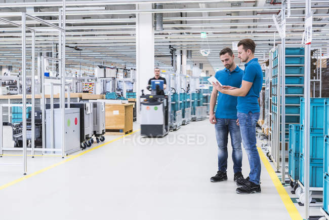 Men with tablet discussing in industrial hall — Stock Photo