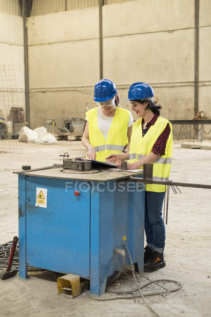Female workers adjusting machine — Stock Photo