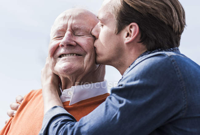 Grandson kissing senior man — Stock Photo