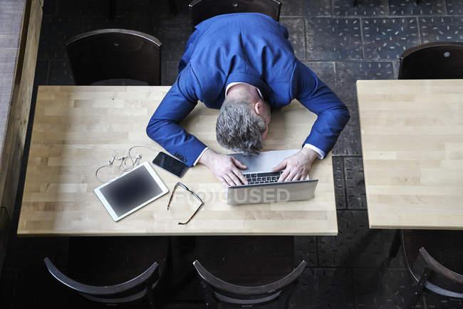 Empresário exausto deitado na mesa no café — Fotografia de Stock