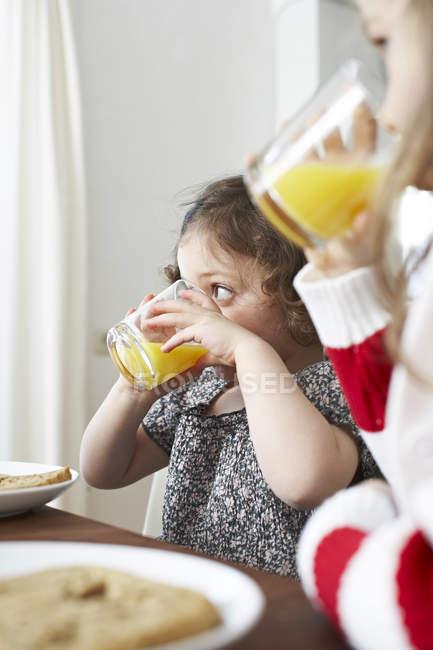Little girls drinking orange juice — Stock Photo