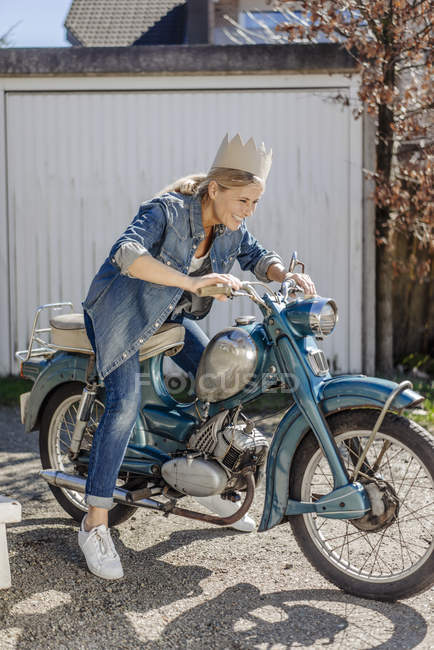 Woman sitting on vintage motorcycle — Stock Photo