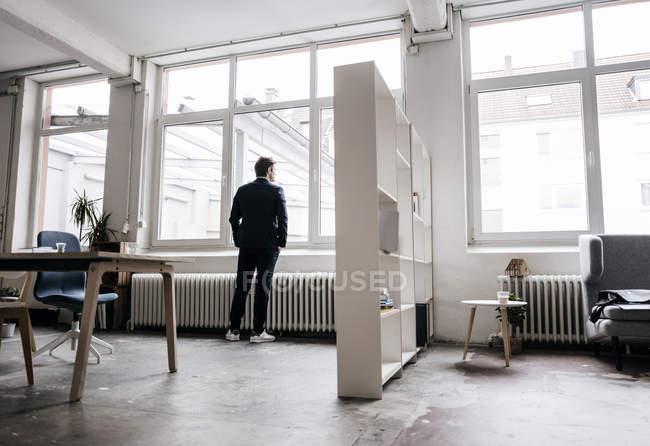 Uomo d'affari in piedi alla finestra — Foto stock