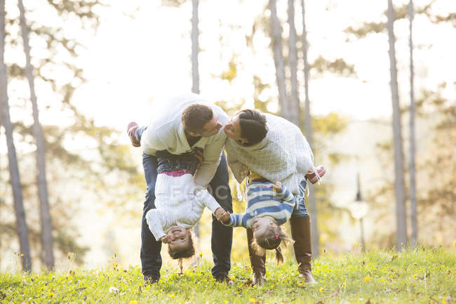 Couple kissing and holding their two daughters upside down — Stock Photo