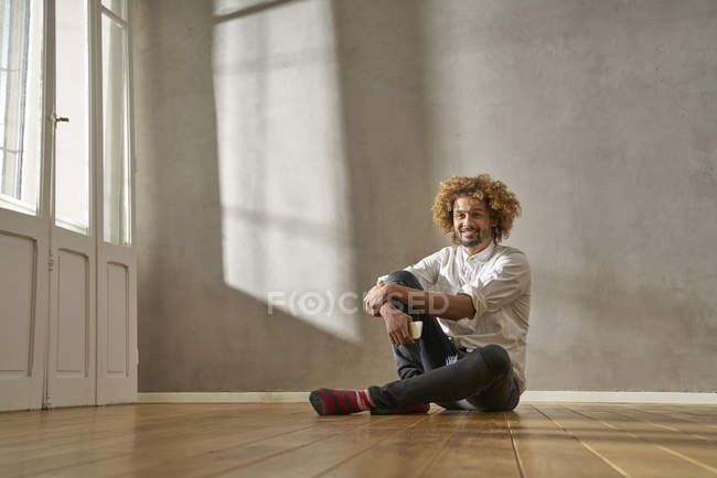Smiling young man sitting in a room — Stock Photo