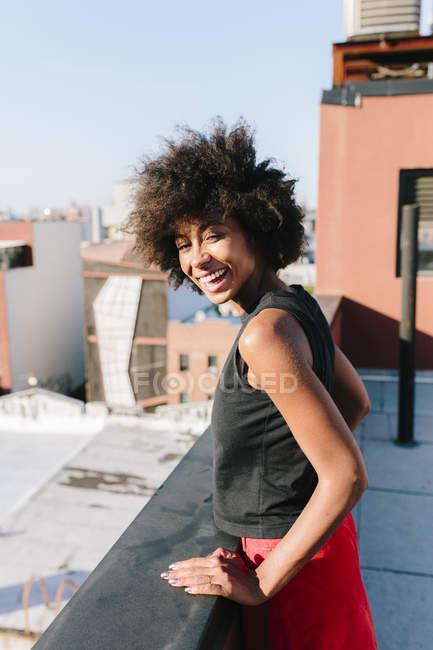 Стороні портрет молоду жінку, що стоїть на даху тераса — стокове фото