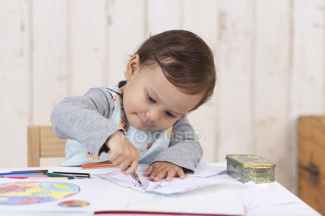 Маленькая девочка рисует цветными карандашами — стоковое фото