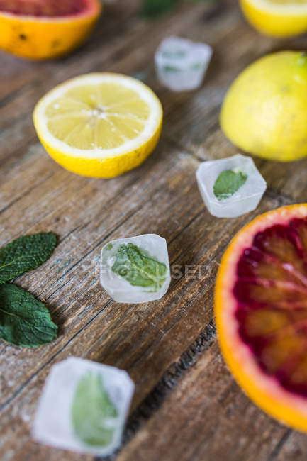 Closeup view of sliced lemons and orange with mint leaves — Stock Photo