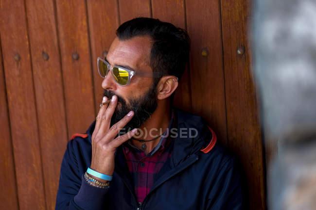 Portrait of man wearing mirrored sunglasses smoking cigarette — Stock Photo