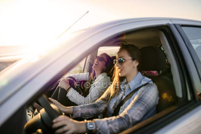 Porträt zweier junger Frauen, die bei Sonnenuntergang im Auto unterwegs sind — Stockfoto