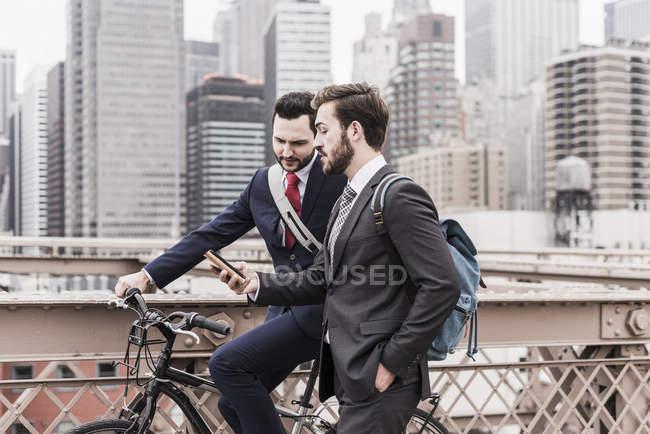 USA, New York, ponte di Brooklyn, Due uomini d'affari a piedi in città con bicicletta e smartphone — Foto stock