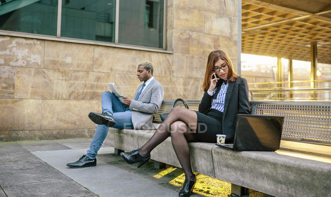 Young businessman and businesswoman sitting on bench with smartphone and newspaper — стоковое фото