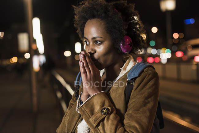 Jovem mulher ouvindo música com fones de ouvido enquanto espera na parada de bonde — Fotografia de Stock