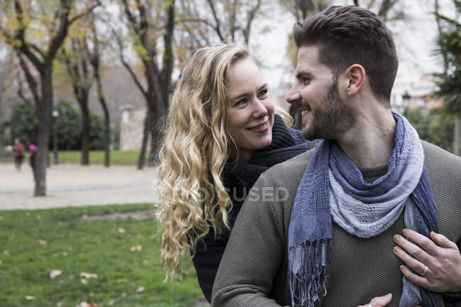 Пара улыбающихся, смотрящих друг на друга в парке — стоковое фото