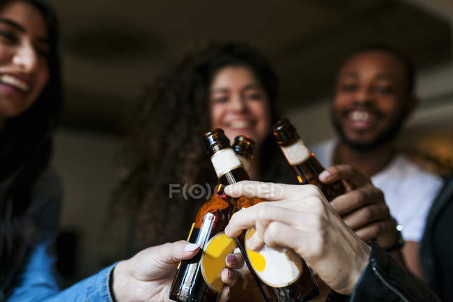 Cropped portrait of young friends toasting with beer bottles — Stock Photo