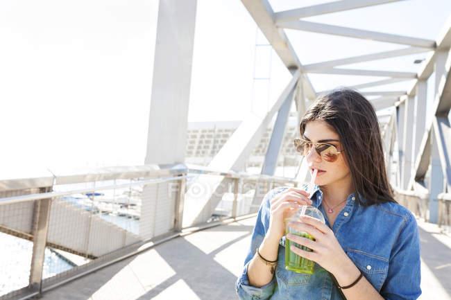 Женщина с напитком стоит на мосту — стоковое фото