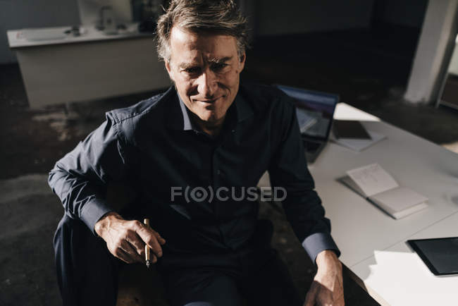 Businessman sitting at desk in office — Stock Photo