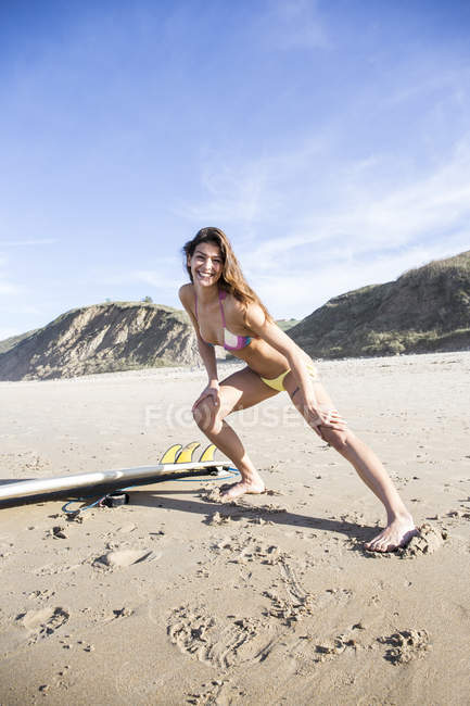 Young woman exercising at sandy beach warming up before surf session — Stock Photo