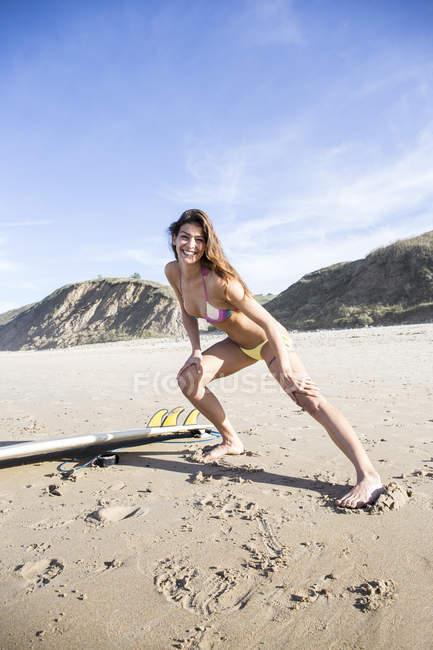 Jeune femme exerçant à la plage de sable échauffement avant la session de surf — Photo de stock