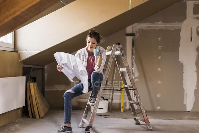 Портрет молодой женщины, рассматривающей план строительства — стоковое фото